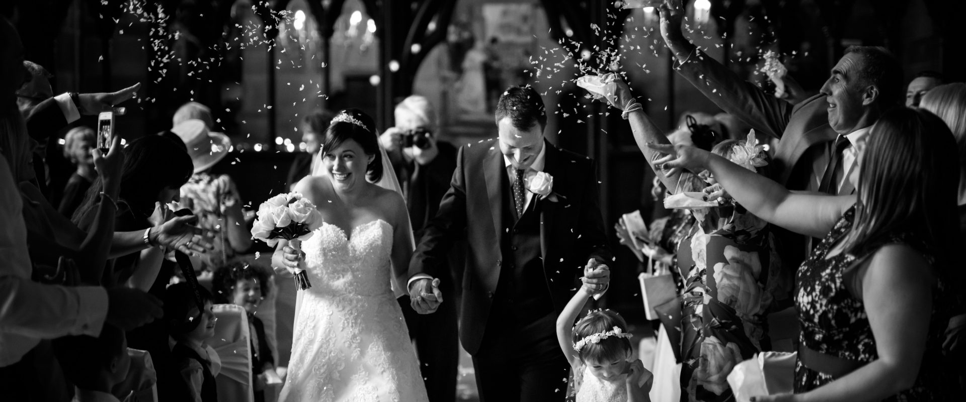 black and white confetti shot indoors as bride and groom walk down the aisle