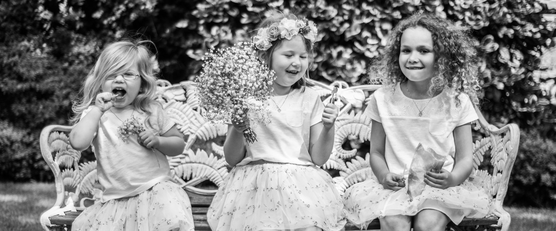 black and white shot of three flowergirls having fun sat on bench