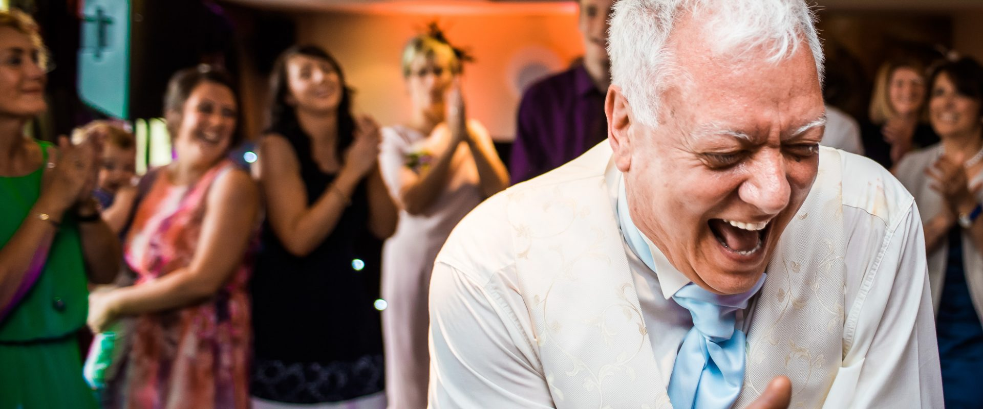 father of the bride laughing hysterically with guests in background