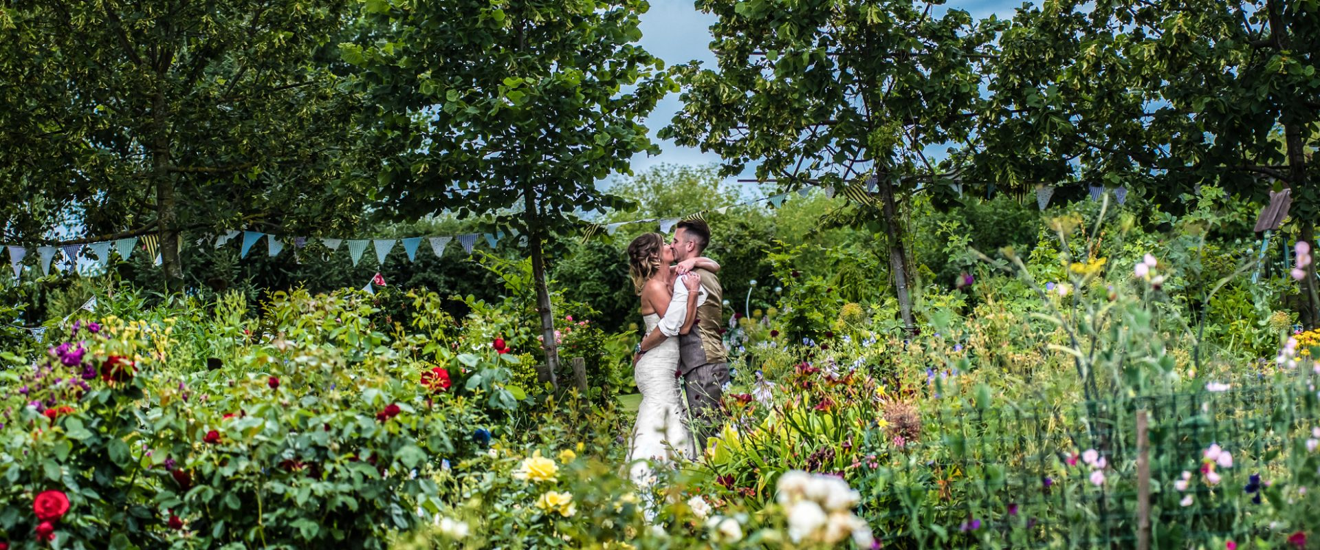 Bride and groom kissing amongst beautiful foliage in floral media