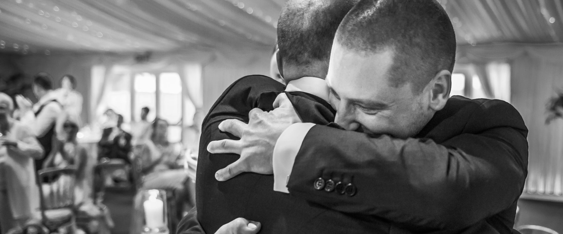 groom hugging best man during speeches, black and white