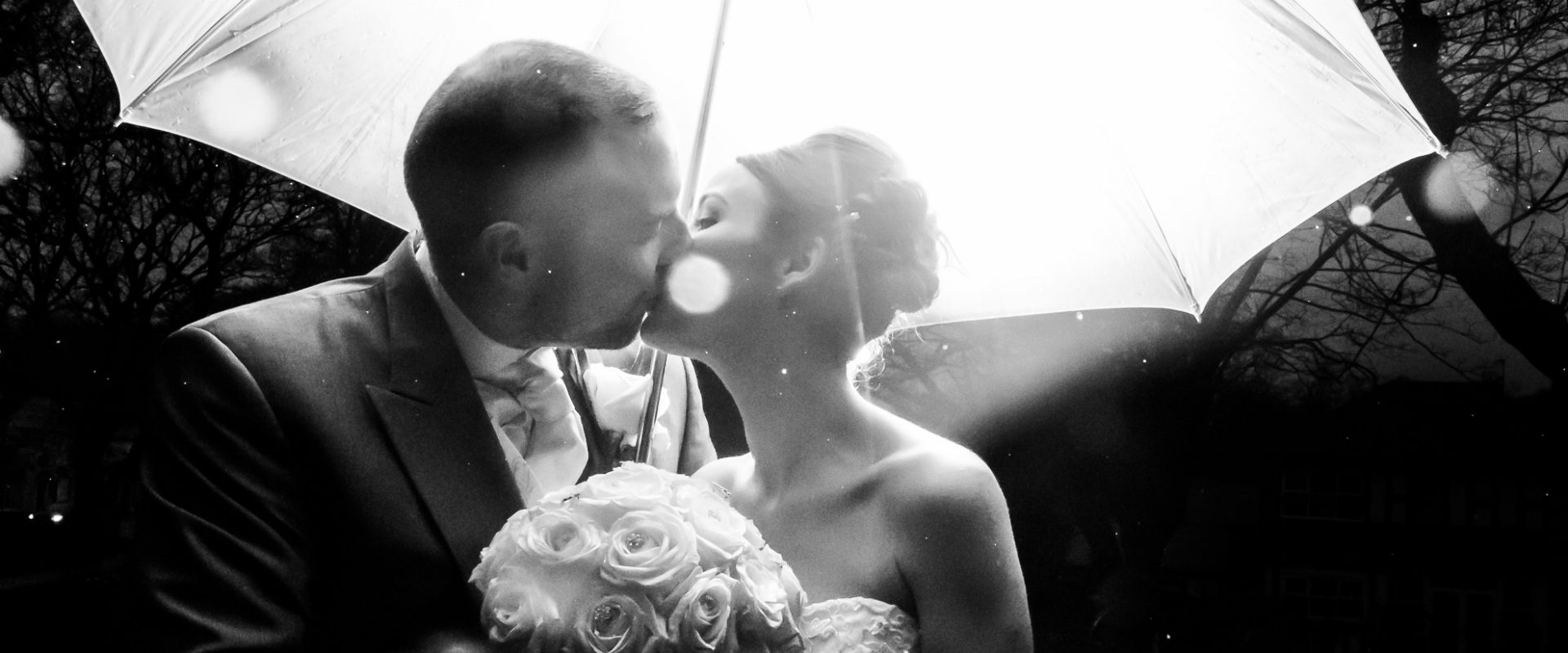 black and white shot of bride and groom kissing under a backlit umbrella in the rain