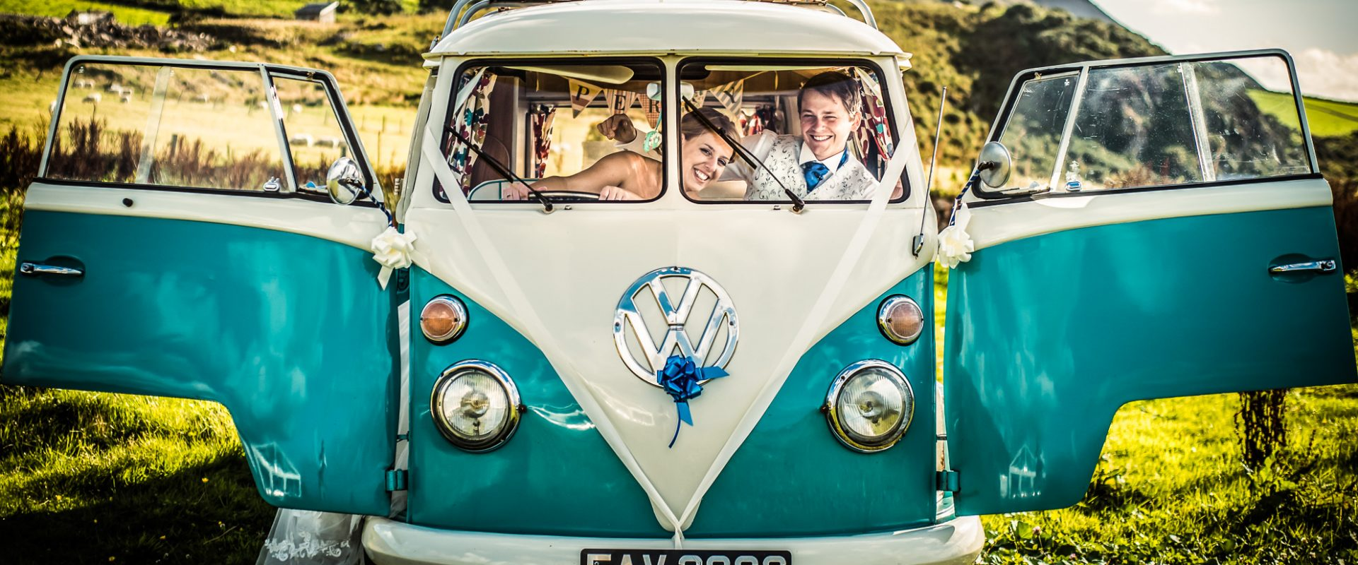 wide shot of bride and groom in VW camper van, front on, with doors open, farm and hills in background. bride is pretending to drive and leaning into groom, groom has arm around her shoulder. Both laughing and looking at camera
