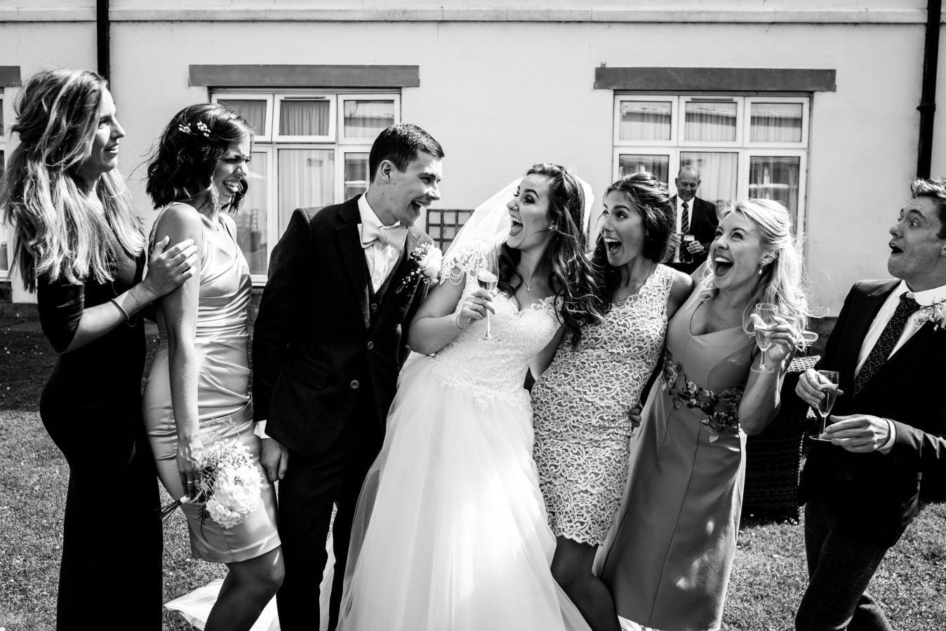 Bride-and-groom-in-grounds-with-friends-dunkenhalgh-hotel