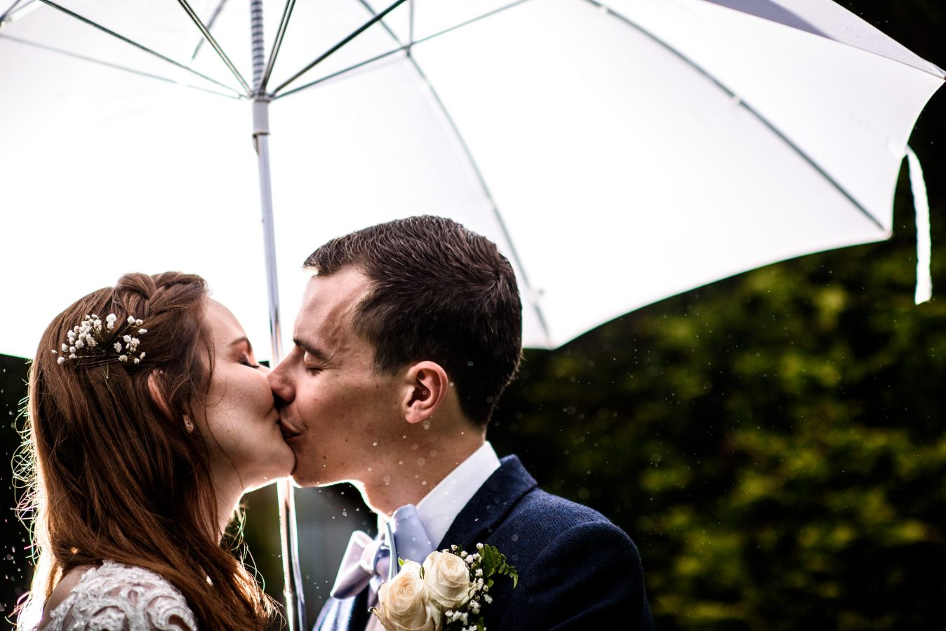 Bride-and-groom-kiss-under-umbrella-dunkenhalgh-hotel