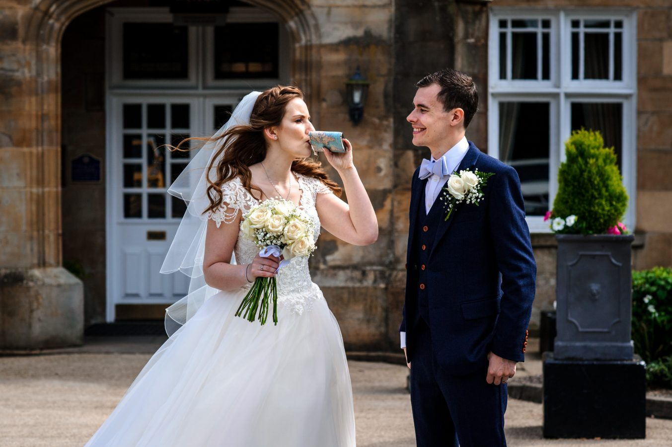 Bride-and-groom-outside-drinking-whiskey-dunkenhalgh-hotel