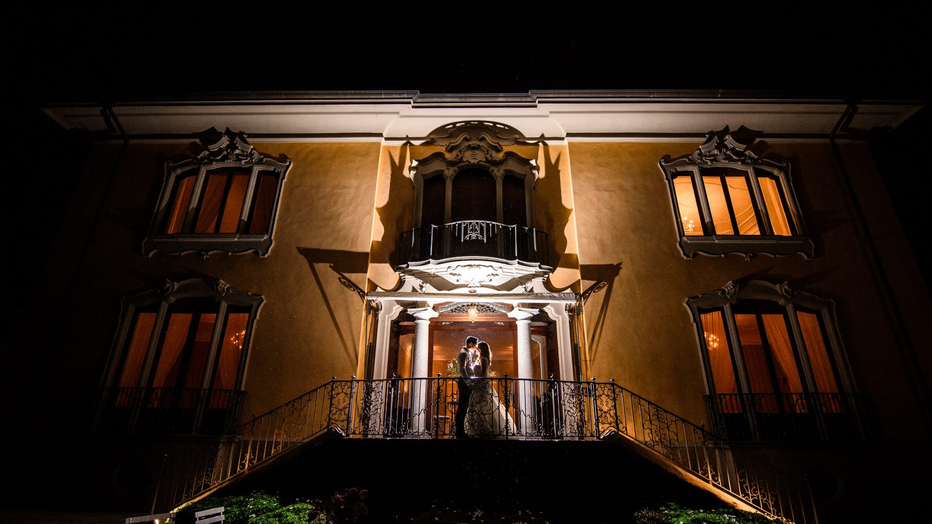 bride and groom kissing outside wedding venue at night