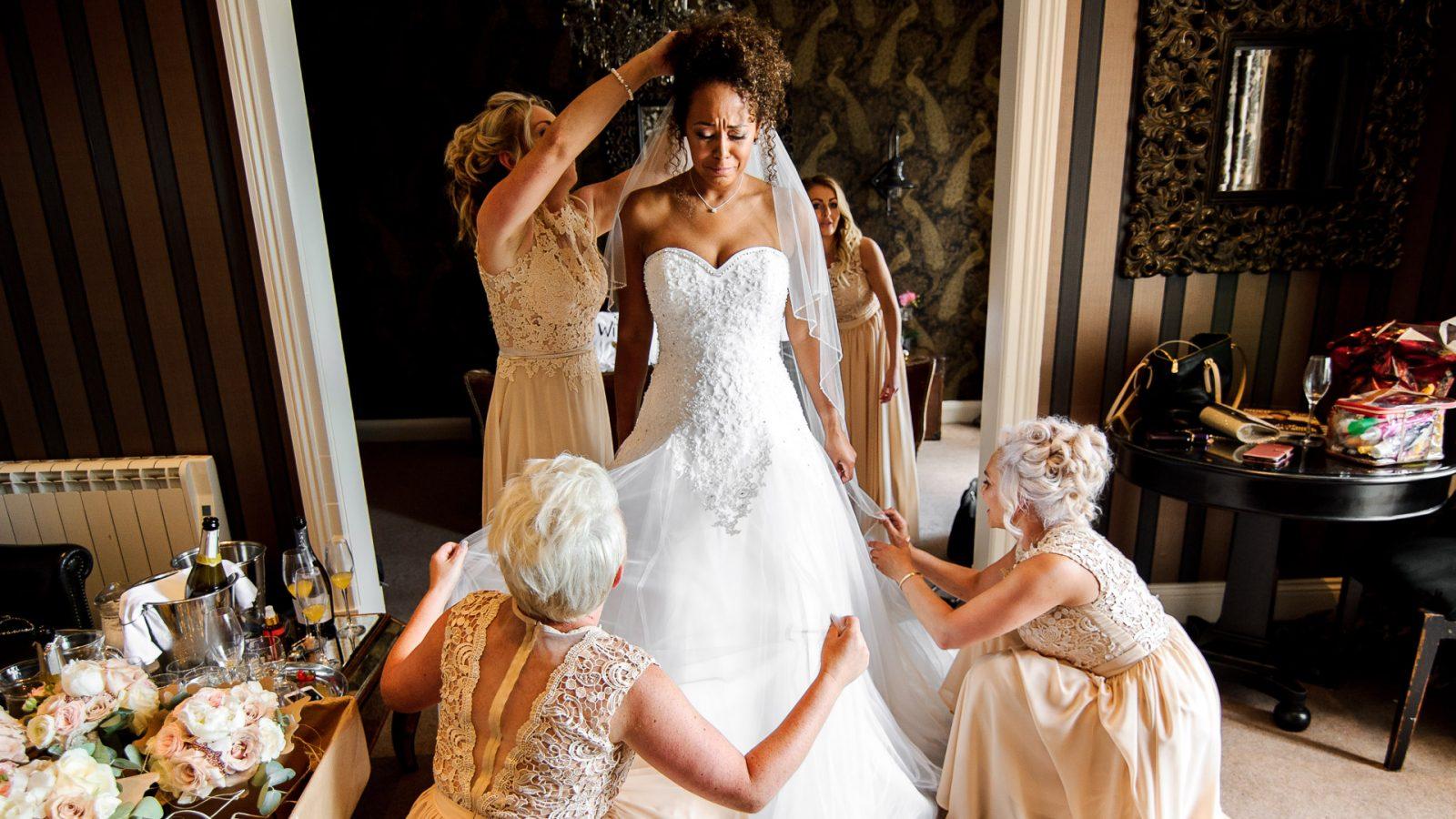 best-wedding-photos-2017-kimberley-and-joseph-bridesmaids-helping-bride-with-dress