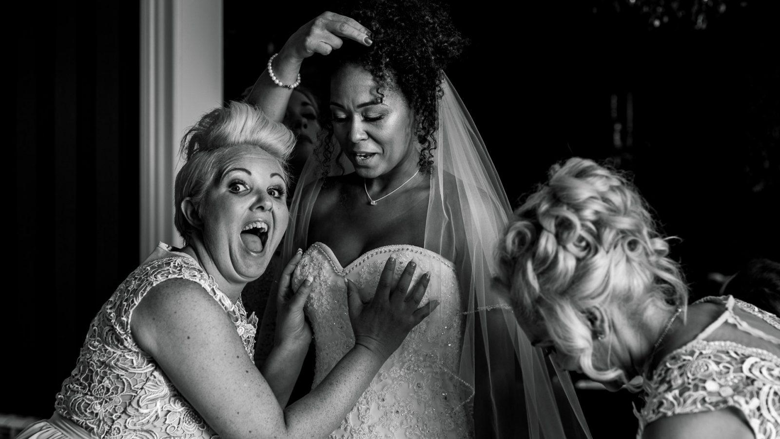 kimberley-and-joseph-wedding-bridesmaids-helping-bride-into-wedding-dress